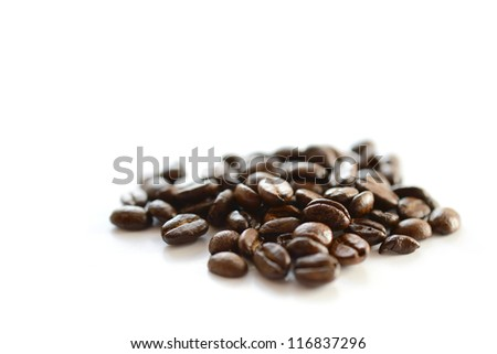 Studio macro image of dark aromatic coffee beans against a white background. Copy space. - stock photo