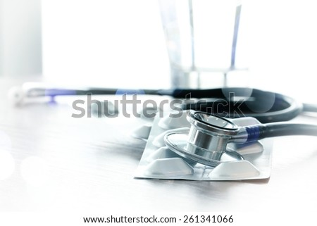 Studio macro of a stethoscope and pills with shallow DOF evenly matched abstract on wood table background copy space