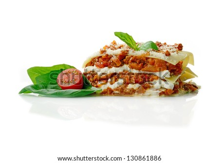Studio macro of freshly prepared lasagne, basil leaves and tomatoes with soft shadows on a white surface. Copy space. - stock photo