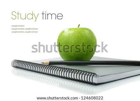 Studio macro of shiny green apple, pencil and new notebook on a white surface. Copy space. - stock photo