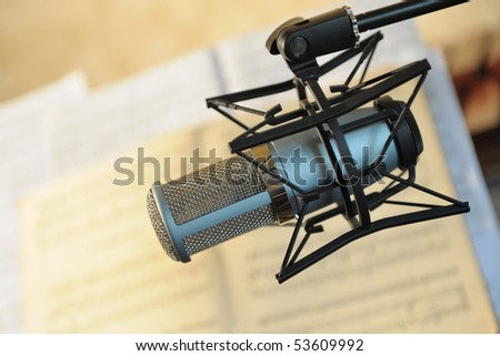 Studio musical microphone. On a background of notes. Selective focus