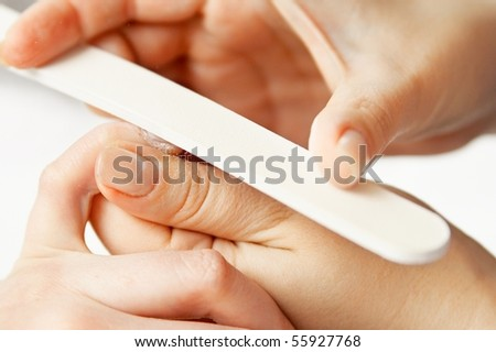 Studio nail - beautician polishing nails - stock photo