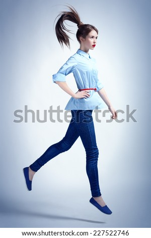 Studio photo in urban style of young woman in a jump. - stock photo