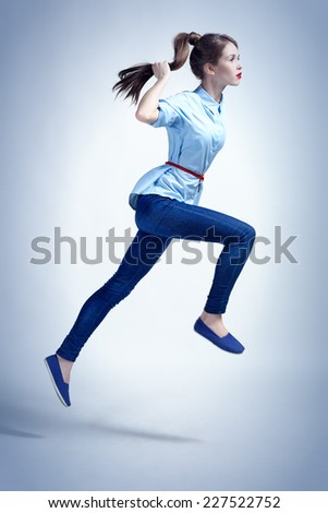 Studio photo in urban style of young woman in a jump.