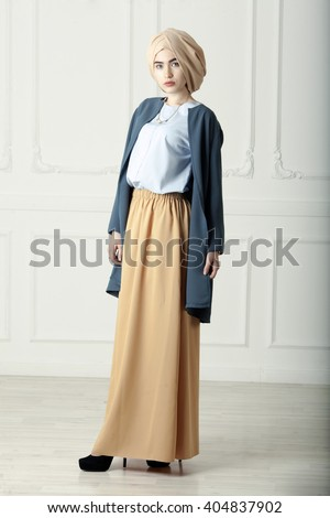 Studio photo of a beautiful young woman eastern type full-length, on a light background, dressed in the Muslim style - stock photo