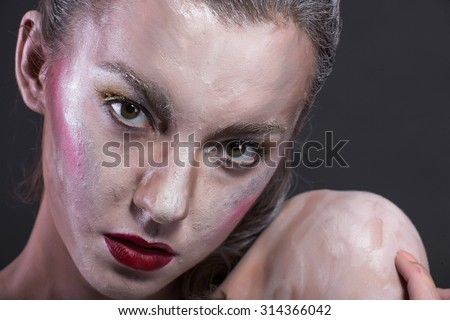 Studio photo of a girl with art make-up on black background