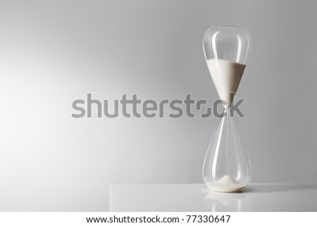 Studio photo of a hourglass on reflective table. - stock photo
