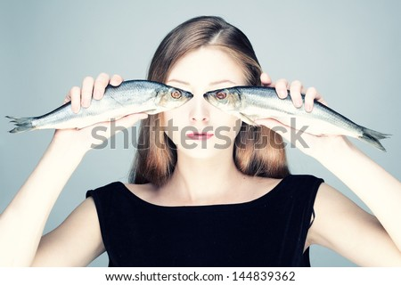 Studio photo of a young woman with the fishes - stock photo