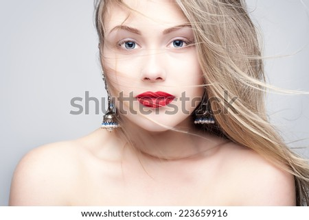 Studio photo of a young woman with wind in her hair. - stock photo