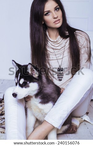 Studio photo of beautiful sexy brunette women with long straight hair wearing in cream sweater, white trousers, necklace and holding a cute little puppy of Husky - stock photo