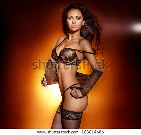 Studio photo of sexy woman in black lingerie posing, looking at camera. Perfect body. - stock photo