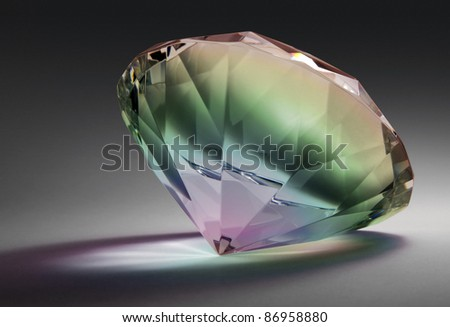 studio photography of a glass diamond in rainbow colors in dark gradient back with clipping path - stock photo