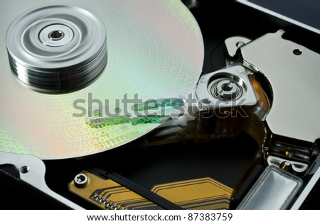 studio photography of a opened hard disk at work with symbolic data