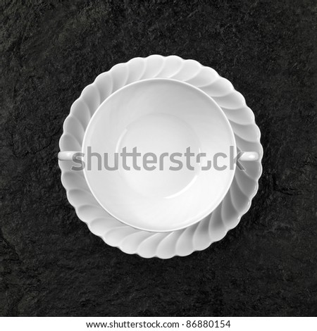 Studio photography of a white porcelain soup plate on dark rough stone surface seen from above - stock photo