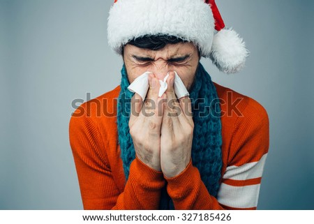 studio picture from a young man with handkerchief. Sick guy isolated has runny nose. man makes a cure for the common cold. Winter concept - Christmas holiday. A man wearing a Santa Claus hat - stock photo