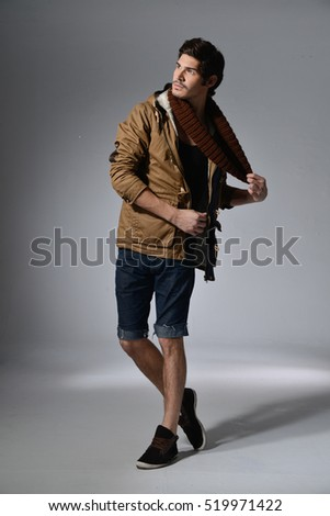 Studio picture of a young and handsome man in short jeans with scarf posing