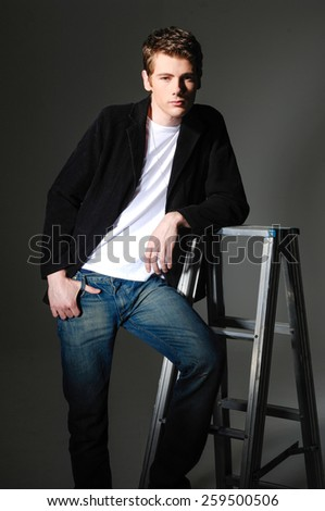 Studio picture of a young man in jeans black background - stock photo