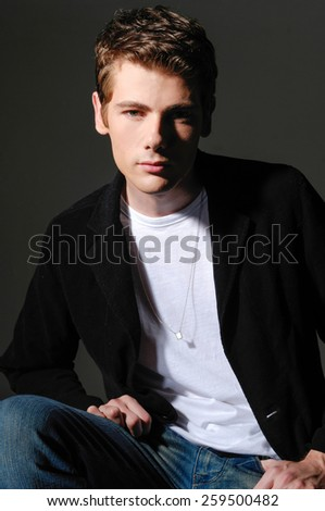 Studio picture of a young man lack background - stock photo