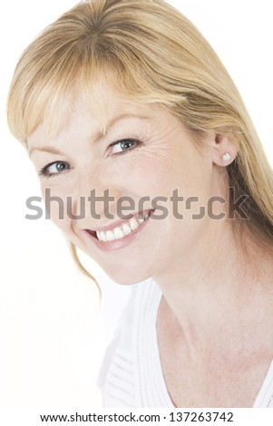 Studio portrait head shot of a happy smiling attractive middle aged blonde woman with perfect teeth
