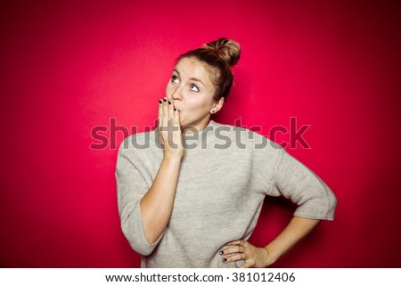 Studio portrait in front of red background of blonde woman - stock photo