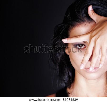 studio portrait of a beautiful brunette hiding face - stock photo