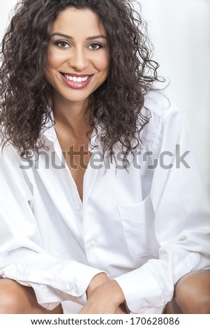 Studio portrait of a beautiful happy young woman smiling wearing an oversized men's white shirt - stock photo