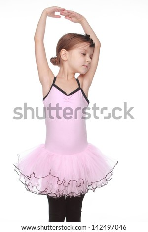 Studio portrait of a beautiful little ballerina in a pink tutu in dance pose on white background - stock photo