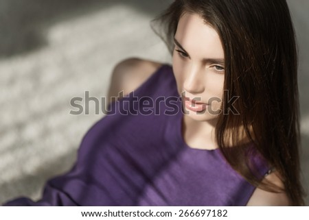 studio portrait of a beautiful sexy girl in a purple shirt against the morning sun