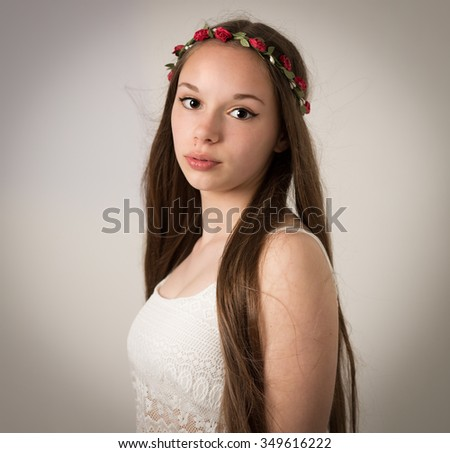 Studio portrait of a beautiful teenage hippie girl with extremely long brown hair wearing a lace white top and a flower wreath isolated against a grey background.