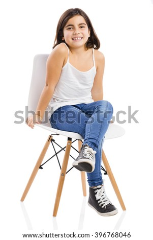 Studio portrait of a beautiful young girl sitting on a chair