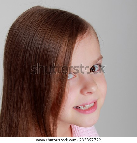 Studio portrait of a beautiful young girl with a sweet smile in a warm knitted dress on a gray background on Beauty and Fashion - stock photo