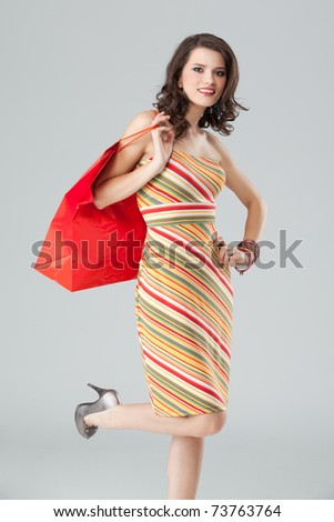 studio portrait of a beautiful young woman, in a colourful outfit, holding in her hand a shopping bag. she is hopping on one foot, laughing and looking very happy. - stock photo