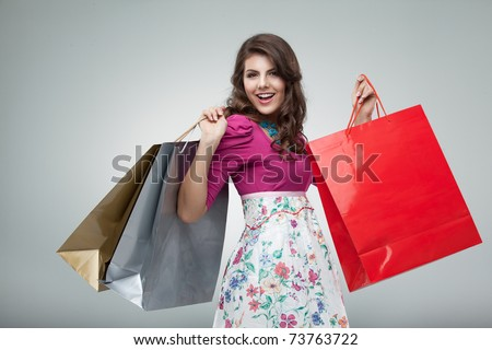 studio portrait of a beautiful young woman, in a colourful outfit, holding in her hands a few shopping bags. she is laughing and looking very happy.