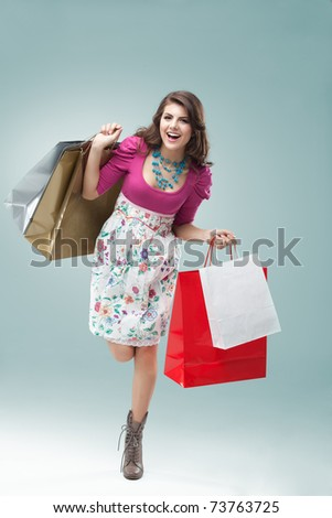 studio portrait of a beautiful young woman, in a colourful outfit, holding in her hands a few shopping bags. she is hopping on one foot, laughing and looking very happy. - stock photo