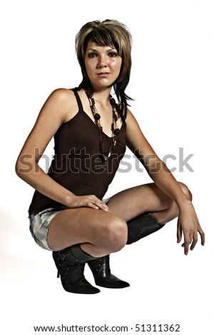 Studio portrait of a beautiful young woman kneeling down with stylish outfit, isolated on a white background. - stock photo