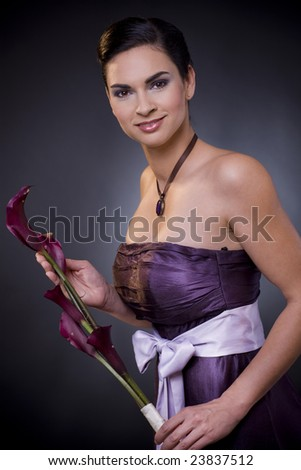 Studio portrait of a beautiful young woman wearing a light purple evening dress holdiing flowers in her hands. - stock photo