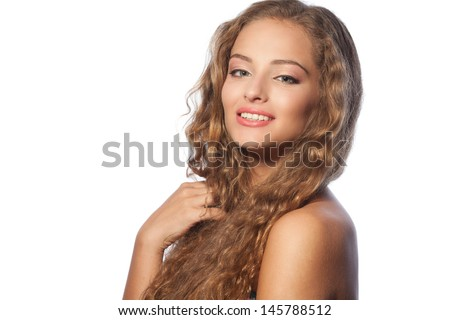 Studio portrait of a beautiful young woman with natural makeup, perfect skin and gorgeous curly hair  - stock photo