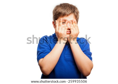 Studio portrait of a blond kid covering his face with both hands and peeking through his fingers to see - stock photo