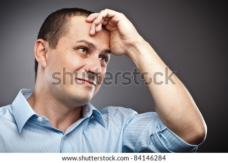 Studio portrait of a businessman with strong migraine - stock photo