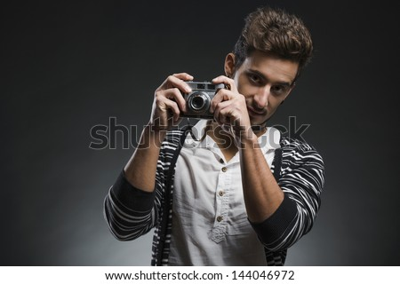 Studio portrait of a fashion young man posing with a old photographic camera, over a dark background - stock photo