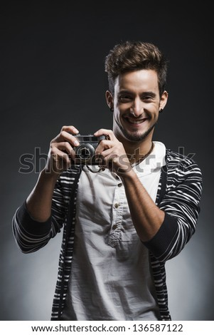 Studio portrait of a fashion young man smiling and posing with a old phootgraphic camera, over a dark background - stock photo