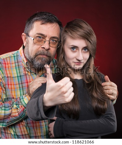 Studio portrait of a father and daughter. Show OK symbol - stock photo