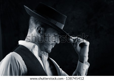 Studio portrait of a handsome young man with a hat in hand on a black background - stock photo