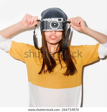 studio portrait of a happy crazy hipster girl with camera in a yellow bike and jeans on white background outdoor - stock photo