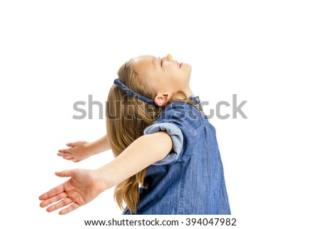 Studio portrait of a happy girl with arms open - stock photo