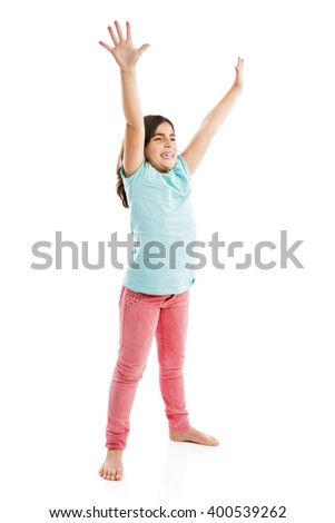 Studio portrait of a happy girl with arms raised on air - stock photo