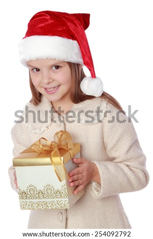 Studio portrait of a happy surprised little girl with long hair in red Santa hat holding a present isolated on white/Image of lovely child in a Santa hat with Christmas present - stock photo