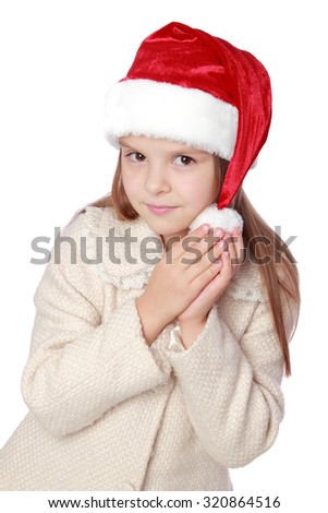 Studio portrait of a happy surprised little girl with long hair in red Santa hat on white background/Image of lovely child in a Santa hat is happy and laughs