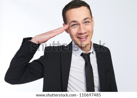Studio portrait of a happy young Caucasian business man smiling and saluting in a suit.