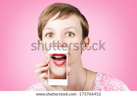 Studio portrait of a happy young girl pulling a surprised funny face while on a video call to girlfriends through a cellphone, over pink background - stock photo